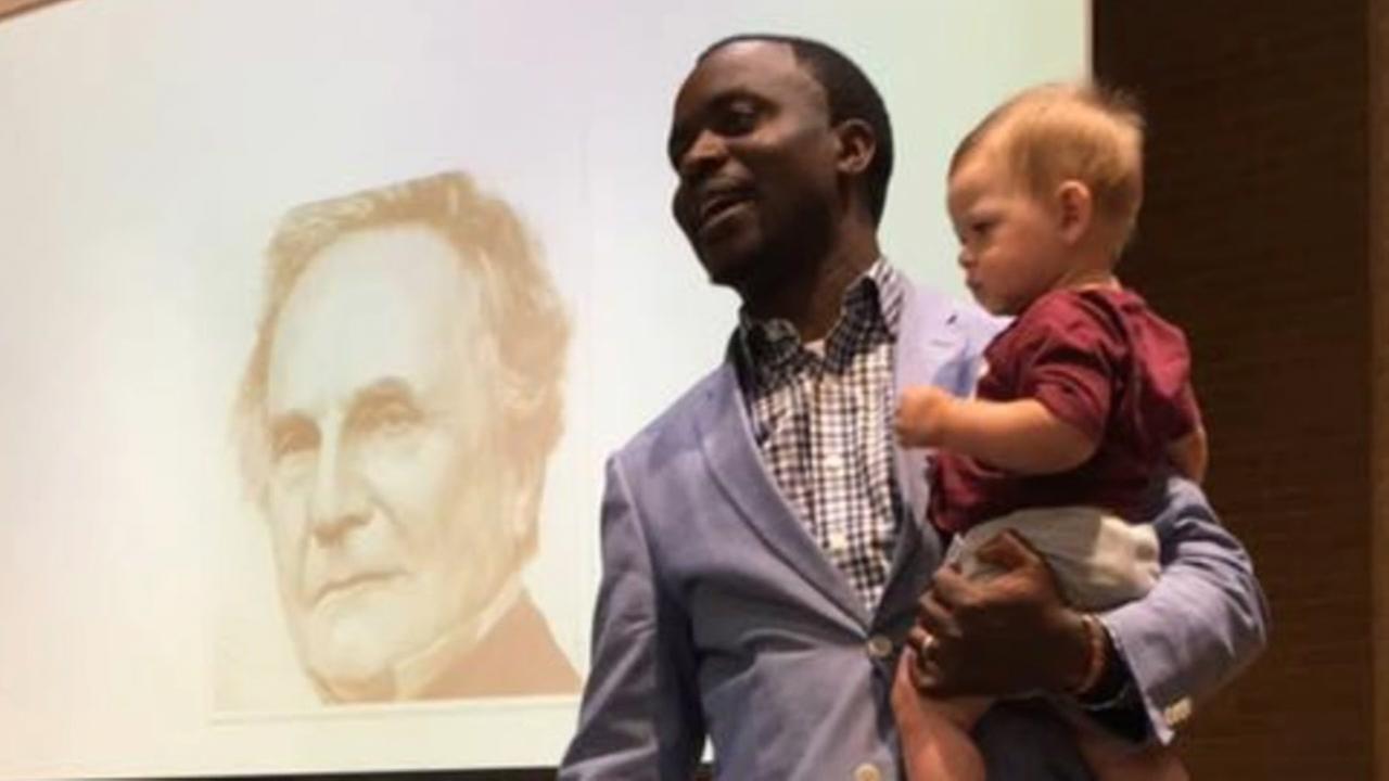 صورة لهنري موسوما وهو يحمل الطفل