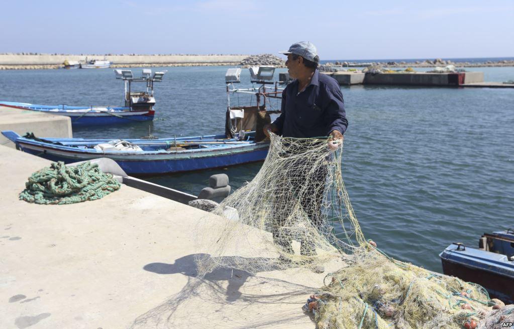 صياد ليبي يعد شباكه للصيد