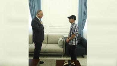 صورة رئيس الوزراء العراقي يستقبل شاباً عذبته الشرطة