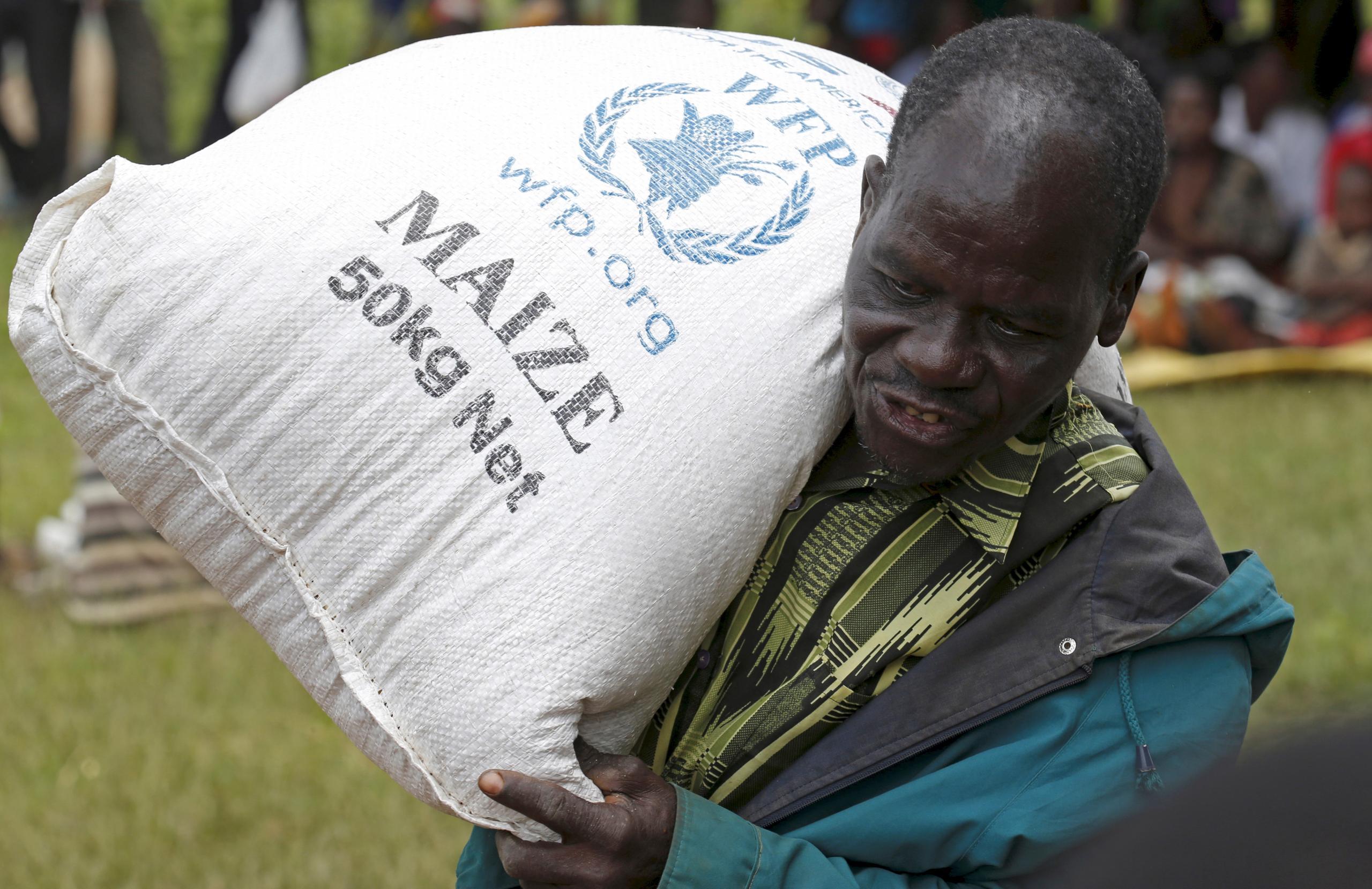 """رجل من """"مالاوي"""" يستلم مساعدة غذائية من برنامج الغذاء العالمي التابع للأمم المتحدة في قرية مزومازي بالقرب من العاصمة ليلونغوي-""""أرشيفية من رويترز"""""""