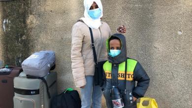 تسيغا طالبة اللجوء الإريترية وابنها إيسي ذو الستة أعوام يستعدان للصعود على متن رحلة إجلاء إنسانية من ليبيا- الصورة نقلا عن المفوضية